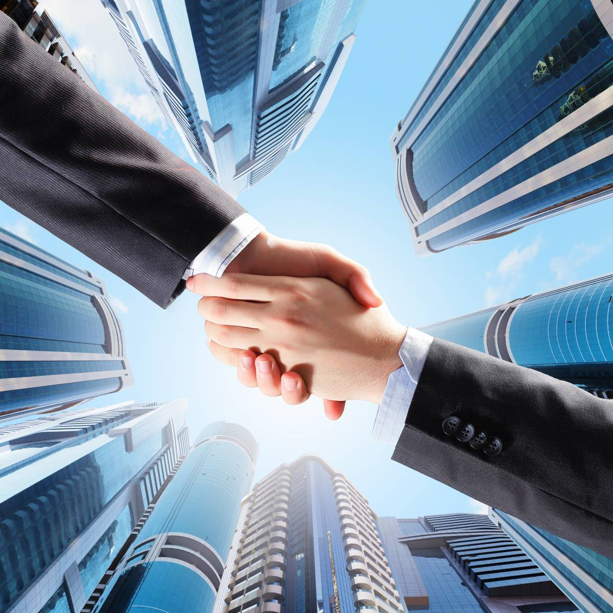 Businessmen shaking hands with vertical city skyline in background